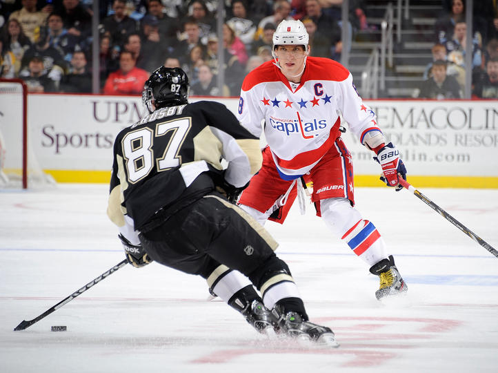 Penguins Sidney Crosby #81 tries to finesse past Capitals Alex Ovechkin (Photo by Joe Sargent/NHLI via Getty Images)