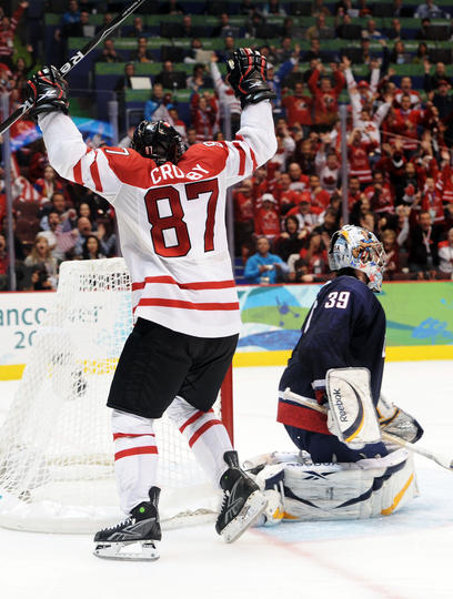 Sidney Crosby #87 of Canada celebrates after scoring the matchwinning goal in overtime whilst a dejected Ryan Miller #39 of the United States looks on during the ice hockey men's gold medal game between USA and Canada on day 17 of the Vancouver 2010 Winter Olympics at Canada Hockey Place on February 28, 2010 in Vancouver, Canada. (Photo by Harry How/Getty Images)