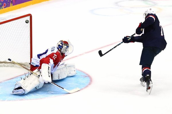 T.J. Oshie beats Russian goalie Sergei Bobrovski to score the game-winning goal for the U.S. in the eighth shootout period. (Clive Mason / Getty Images)
